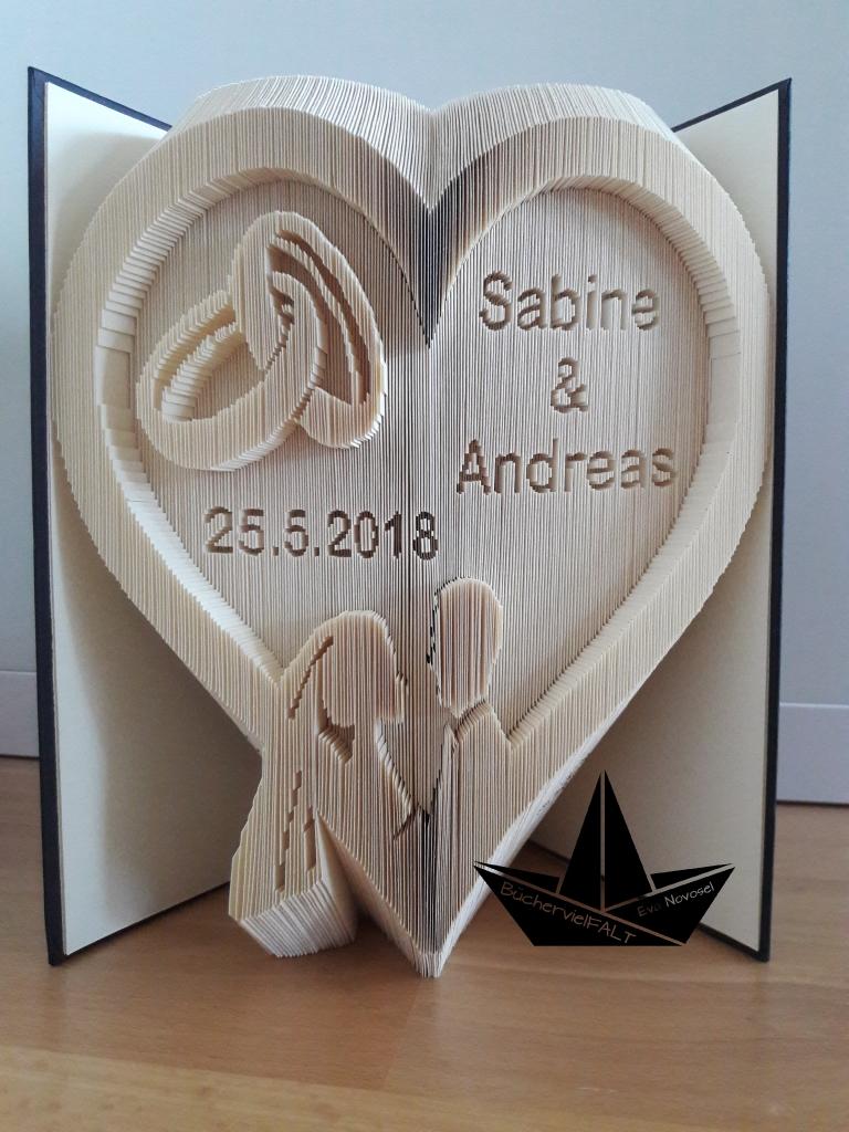 gefaltetes Buch - Hochzeitsherz mit Brautpaar und verschlungenen Ringen
