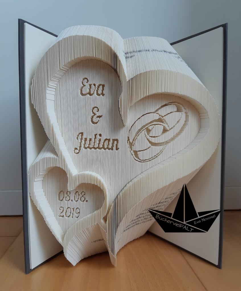 gefaltetes Buch - geschwungenes Hochzeitsherz und verschlungenen Ringen